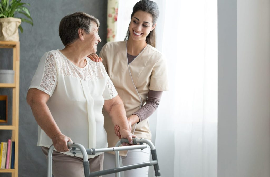A senior woman gets help walking in her apartment from a friendly female staff member