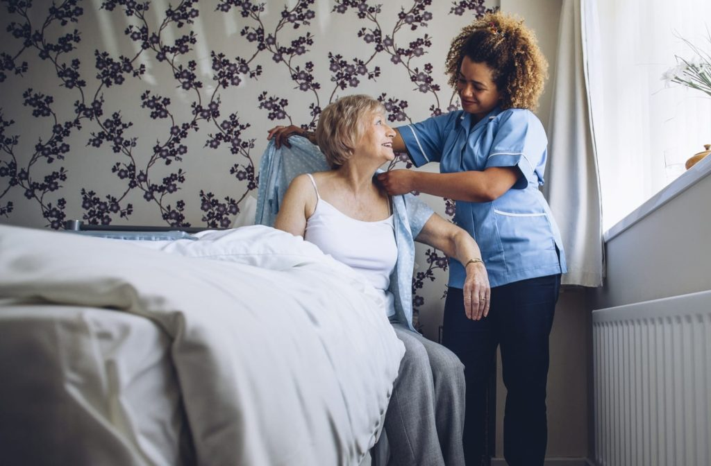 A smiling senior woman receives help getting dressed in a shirt from a friendly staff person